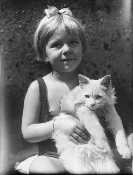 A little girl in a bathing costume, with a bow in her hair, holding up her white cat