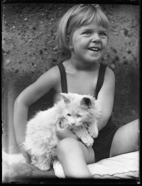 A little girl in a bathing costume smiles gleefully as she cuddles her white cat