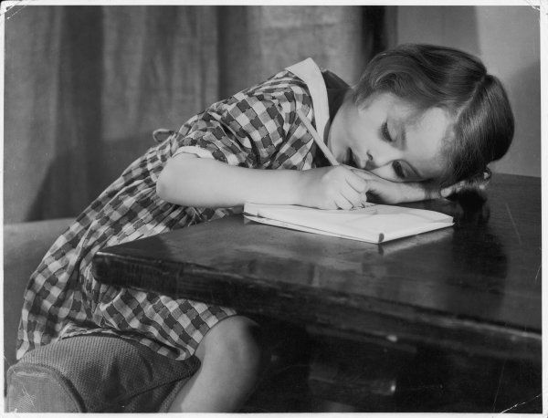 A young girl writes on paper with a pencil
