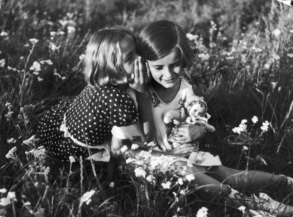 Two pretty little girls in summer dresses, one with a doll, sitting in a field of wild flowers together and whispering secrets