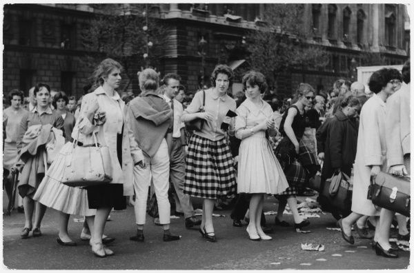 Two fashionably dressed girls cross the street looking rather unfavourably at a girl who is perhaps not so fashionable