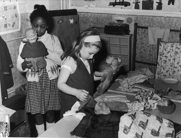 A little black girl and a little white girl playing with dolls and a teddy together, dressing them up in various outfits
