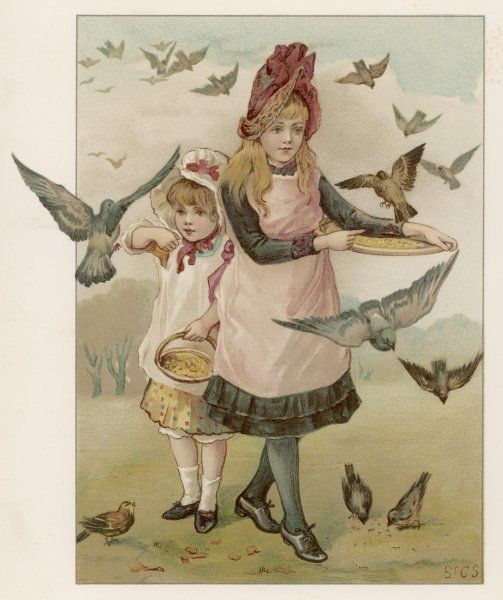 Two girls feed some birds
