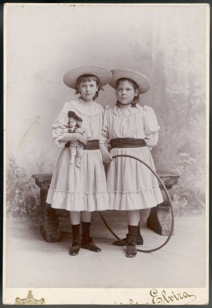 Two German girls in identical yoked dresses with a single scallop edged flounce, full sleeves & sash, sailor hats, socks & patent leather shoes with a bar & shoes roses