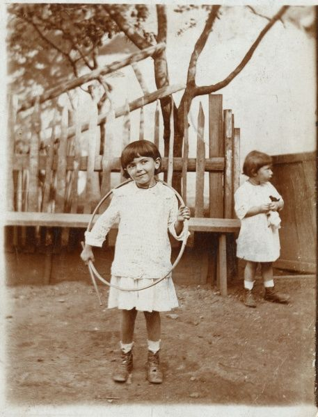 Two girls in a garden or back yard, one with her hoop and stick, the other holding a doll. They are from the settlement of Kostel (also known as Podivin) in South Moravia, now in Czechoslovakia