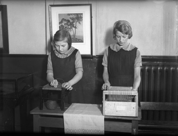 Two girls making chairs or stools at the London County Council Handicraft School. Date: early 1930s