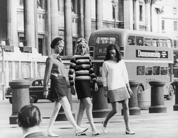 "Take Three Girls Three young women wearing mini skirts in Trafalgar Square, London. A ""No 11"" bus going to Liverpool Street station passes by in the background"