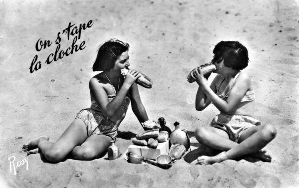 Two girls on a beach have brought a quantity of baguette sandwiches, and three containers of drink, and are busily stuffing themselves