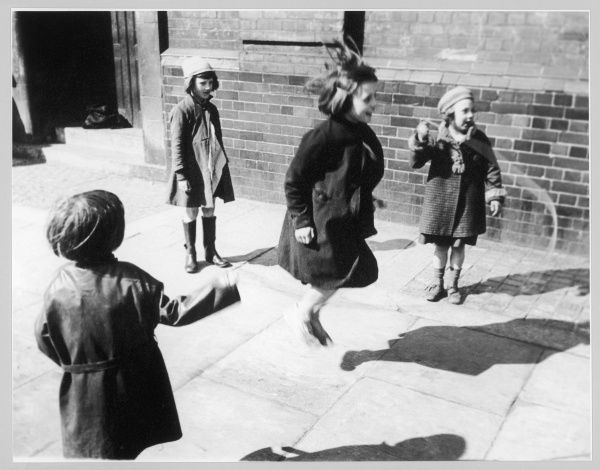 A group of little girls in overcoats playing a game of skipping on the street