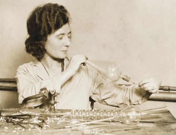 A female glass worker blows glass for use in lamps, chemistry equipment, etc