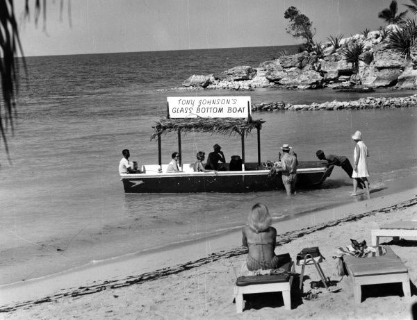 A glass bottom boat trip leaving a beach in Antigua, West Indies. Date: late 1960s