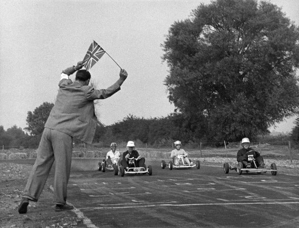 An official waves a Union Jack flag to start the race. Date: 1950s