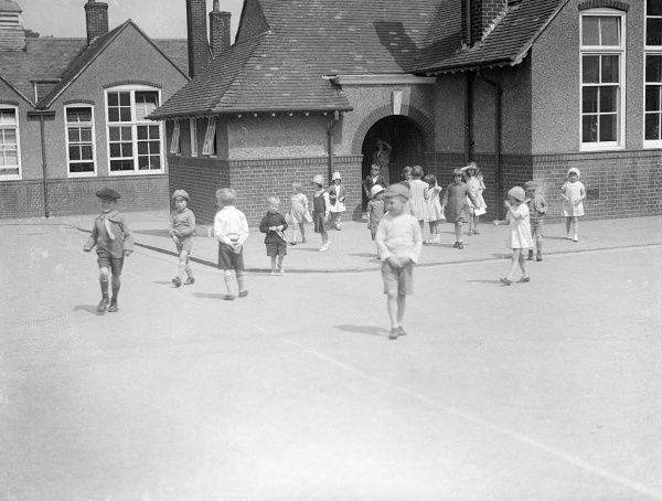 A group of schoolchildren walking into the playground on their way home from school. Date: 1930s