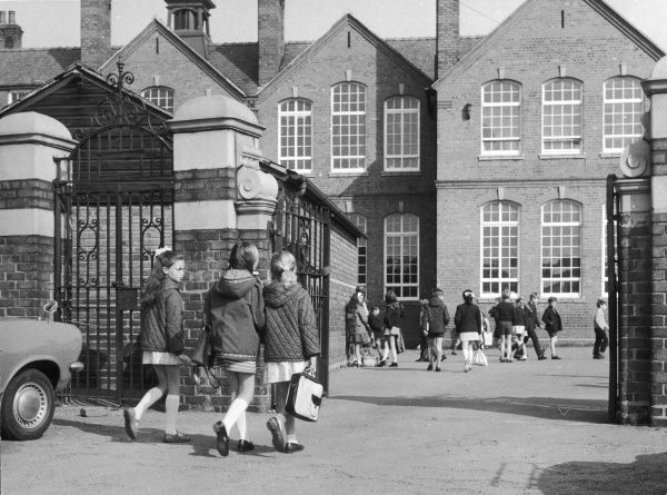 Three little girls going through the school gates into a busy playground with other children milling around it