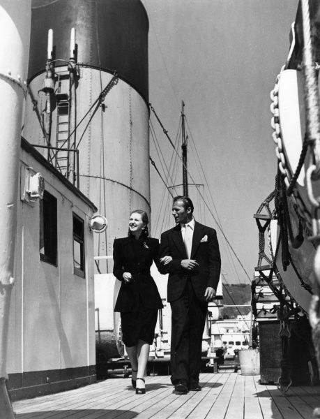 A smartly dressed couple stroll along the deck of the 'Golden Arrow' ferry, connecting luxury trains between Dover and Calais. Date: 1947