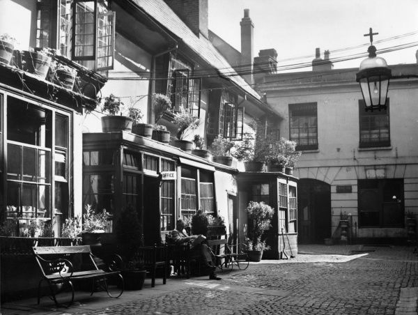 The Golden Cross Inn, Cornmarket, Oxford, England, is the site of the oldest pub in the city. Its landlord was prosecuted for selling blackmarket wine in 1285! Date: 1950s