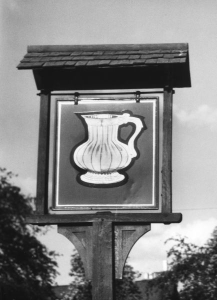 'The Golden Pot' inn sign, which portrays a large golden jug or pot, at Eversley, Hampshire, England