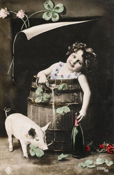 A Czechoslovakian Good Luck postcard, featuring a small girl sat in a barrel holding a bottle of sparkling wine (and spilling a glass of the same), surrounded by large four-leafed clovers, some of which are being eaten by a piglet!