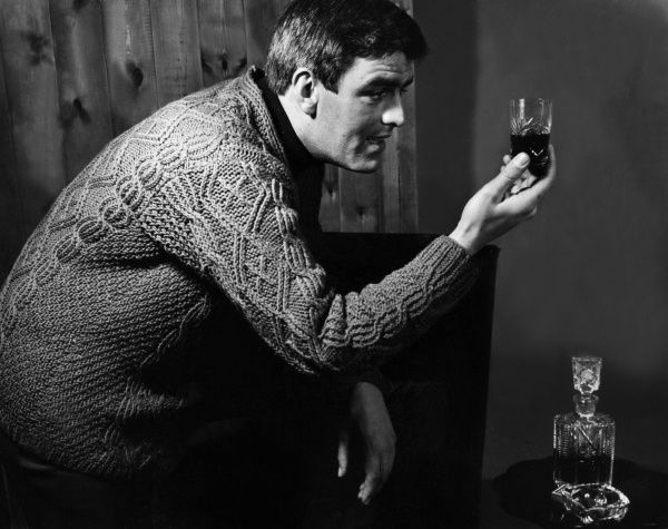 A man wearing a knitted sweater holds up a glass of fine sherry or port he has just poured from a decanter. Date: 1960s