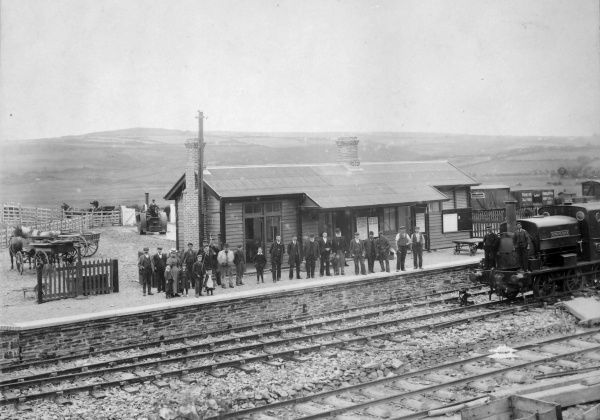 A long line of passengers and staff waiting on the platform at Goodwick Railway Station on the Great Western Railway, Pembrokeshire, Dyfed, South Wales
