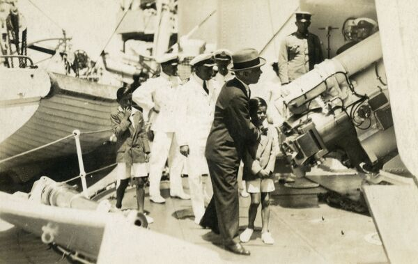 Governor of Arica, Chile takes his son on a tour of the guns on a Chilean Naval vessel, accompanied by the Captain and ship's officers. Date: circa 1920s