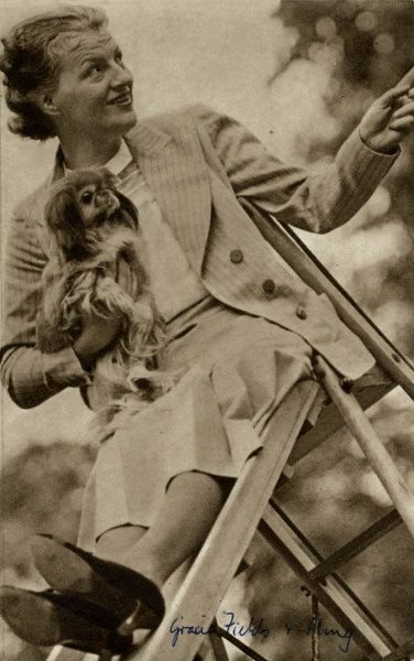 The English singer and actress, Gracie Fields (1898-1979), with her dog Ming, sitting at the top of a slide. Date: 1938