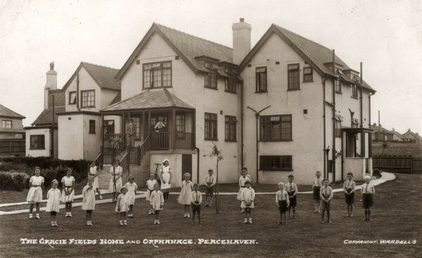 Children and staff stand in front of the orphanage and children's home at Peacehaven in East Sussex