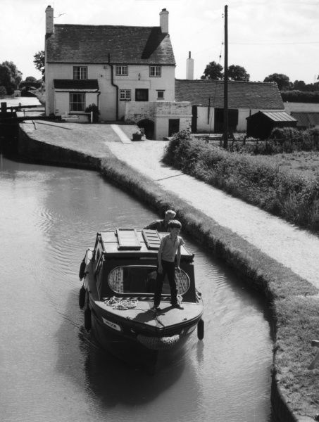 A happy little boy aboard 'The Folly' motor cruise boat on the Grand Union Canal at Napton, Warwickshire, England. Date: 1960s
