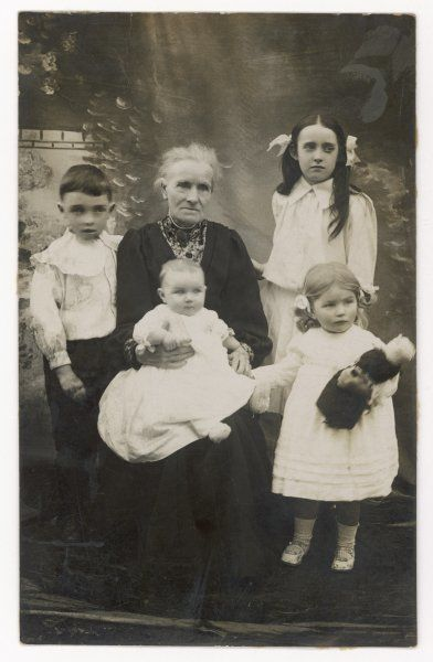 A rather serious-looking grandmother with her four grandchildren