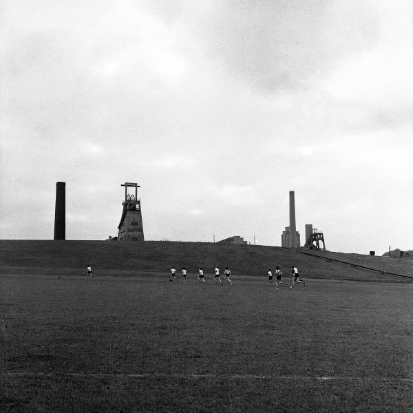 Grassmoor, North Derbyshire Area Training Centre for miners was opened in 1957. A group of trainees in shorts run across a field, the colliery sits on the hillside above