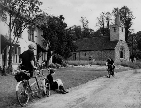Tour cyclists admire the Norman church at Great Canfield, Essex, England, noted for its 13th century wallpainting over the altar. Date: 1930s