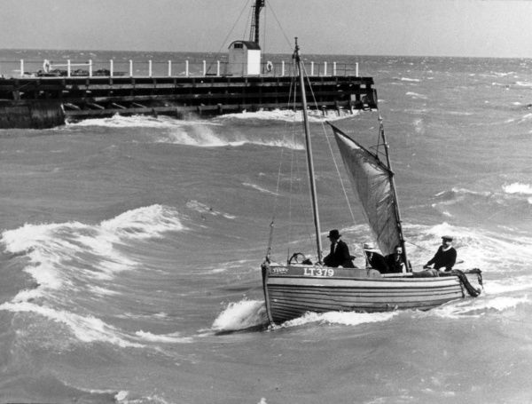 A 'shrimper' (small shrimp fishing boat) enters the harbour at Great Yarmouth, Norfolk, England, in a rough sea. Date: 1950s