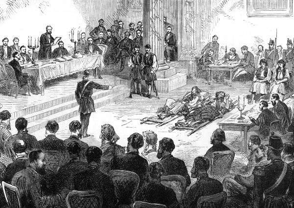 Two brigands lie in the middle of a courtroom in Athens, listening to the charges read out against them. Date: 1870