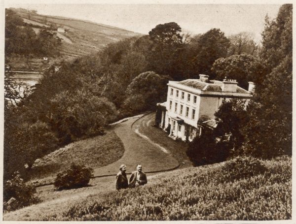 Photograph showing Greenway House in Devon, which was the home of Agatha Christie and Max Mallowan in 1946. The couple can be seen (just) in the foreground of this image