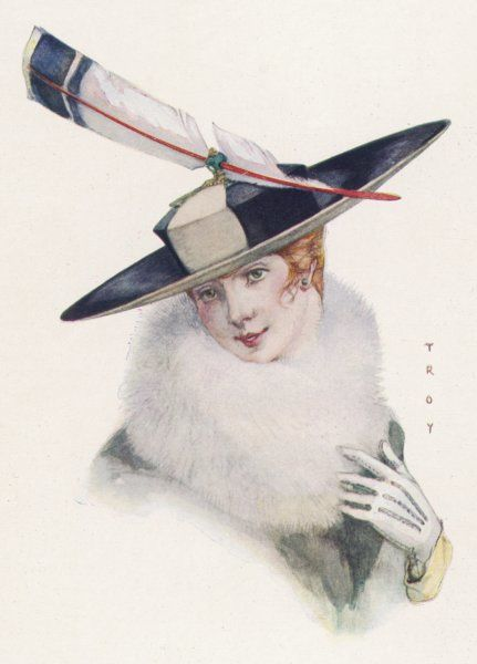 A fetching grey & black felt hat with a low flat crown & broad up-turned brim ornamented with a dyed & shaped feather & a jewelled device for holding it
