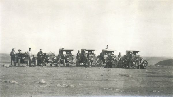 A line of six ground support vehicles lined up in the desert, somewhere in Iraq, with arab drivers and others