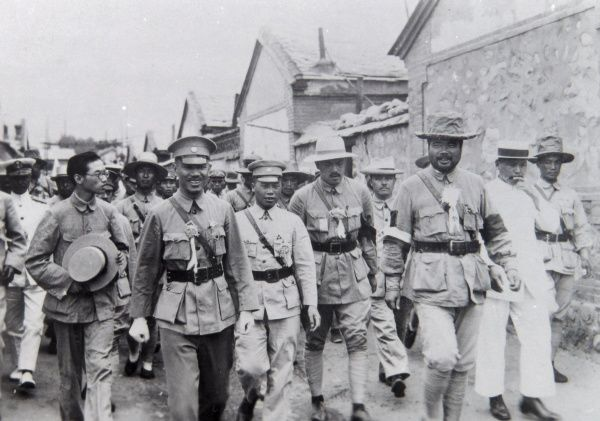 A large group of Eastern dignitaries, some wearing uniform, walking along a street somewhere in the Far East