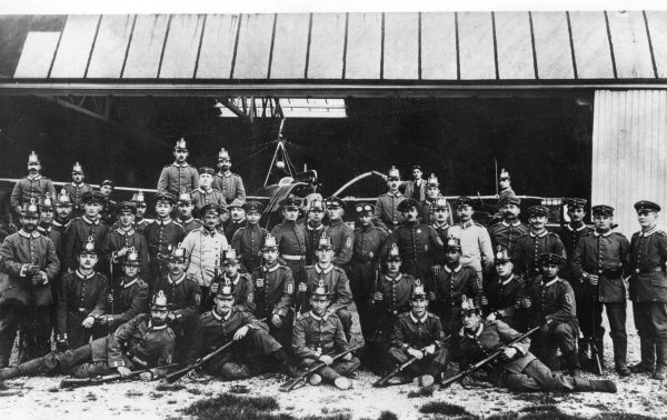 A group photo of officers and men of No.2 Squadron, German Air Force, at the start of the First World War. Some of them are wearing Jager shakos (cylindrical military caps), and have Prussian Guard stripes on their collars. Date: 1914