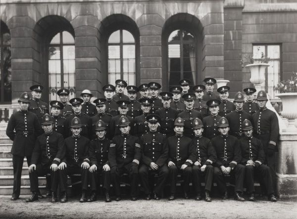 A group of policemen pose for their photograph at Battersea in south west London. They are all in uniform, some wearing helmets, others (the Special Constables) in peaked caps, and one man wears a tin helmet