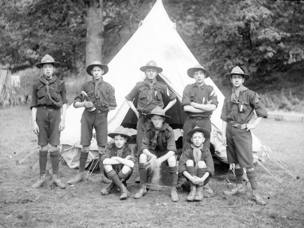 A group of eight boy scouts pose for their photo in a field, in front of a tent. One of them is holding a bugle, no doubt used to wake them all up in the morning