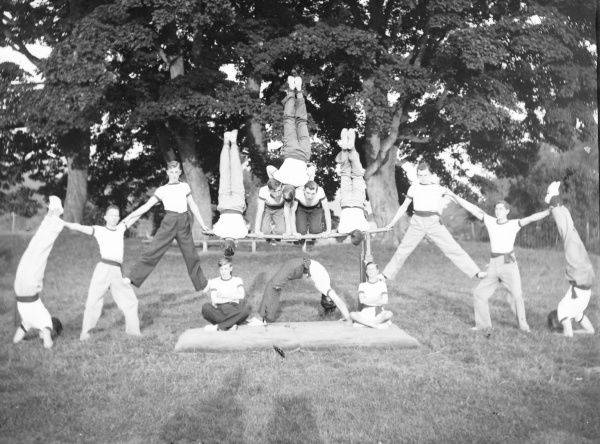 A group of young servicemen doing acrobatics in a field, perhaps as part of their military training