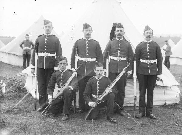 A group of four soldiers and two cadets at a training camp, posing for their photo outside a tent. They are all in full uniform, and are holding rifles