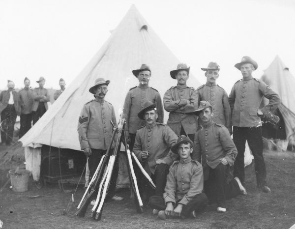 A group of eight soldiers at a training camp, posing for their photo outside a tent. A stook of rifles stands in front of them. Four more soldiers can be seen in the background on the left. Most of the men are wearing bush hats