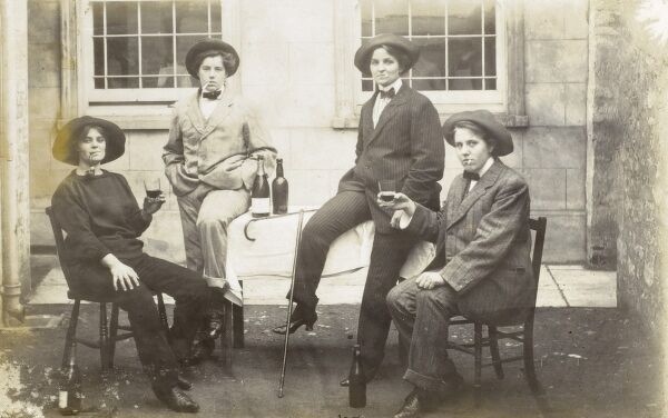 Group of Transvestite Ladies. Four women dressed as men lounge around a table, drinking champagne and beer and dressed in sharp men's suits nd soft hats. The lady of the left appears to be wearing a fisherman's jumber and is smoking a curved pipe