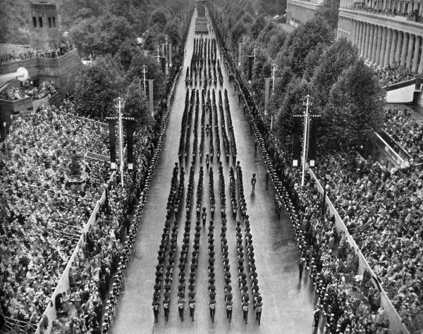 This view of the Mall, from Admiralty Arch, shows files of Guards marching in formation as they near Buckingham Palace.  1953