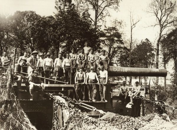 British gunners posing for their photo with a 12 inch Howitzer named Bunty, on the Western Front in France during the First World War. The crew are stripped to the waist, ready for hot work. Date: 1914-1918