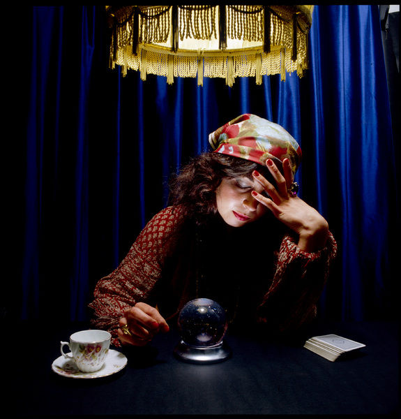 A Gypsy fortune teller gazes deeply into a crystal ball. Other tools of divination are nearby, the drained teacup for reading the tea leaves, and a pack of cards for the tarot