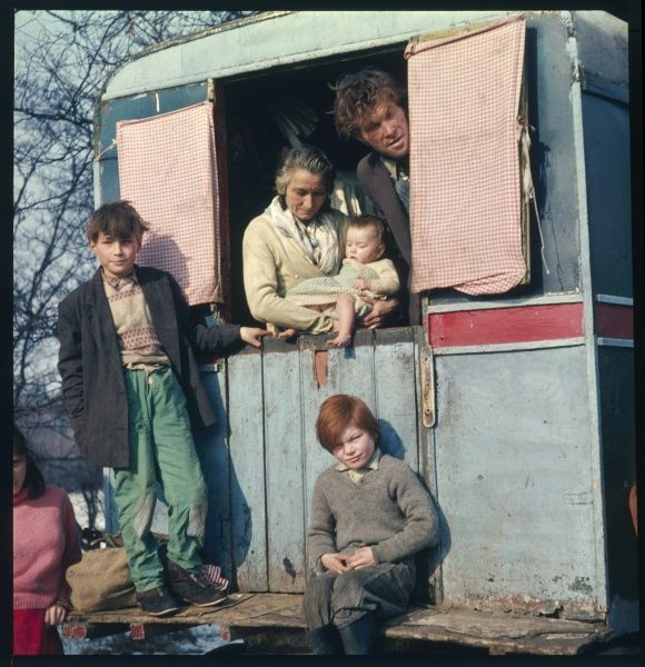 Three generations of a gypsy family stand in, on and around their caravan in this winter scene in a traveller encampment