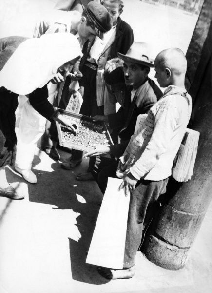 Tourists haggling over jewellery at a bazaar in Turkey. Date: 1930s