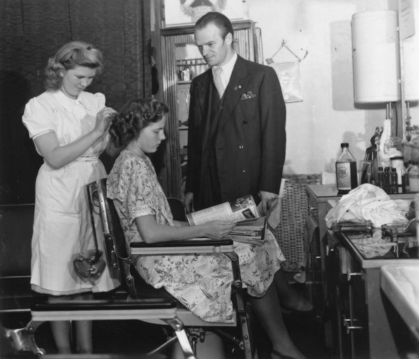 A girl pass the test as hairdresser before a male inspector. Date